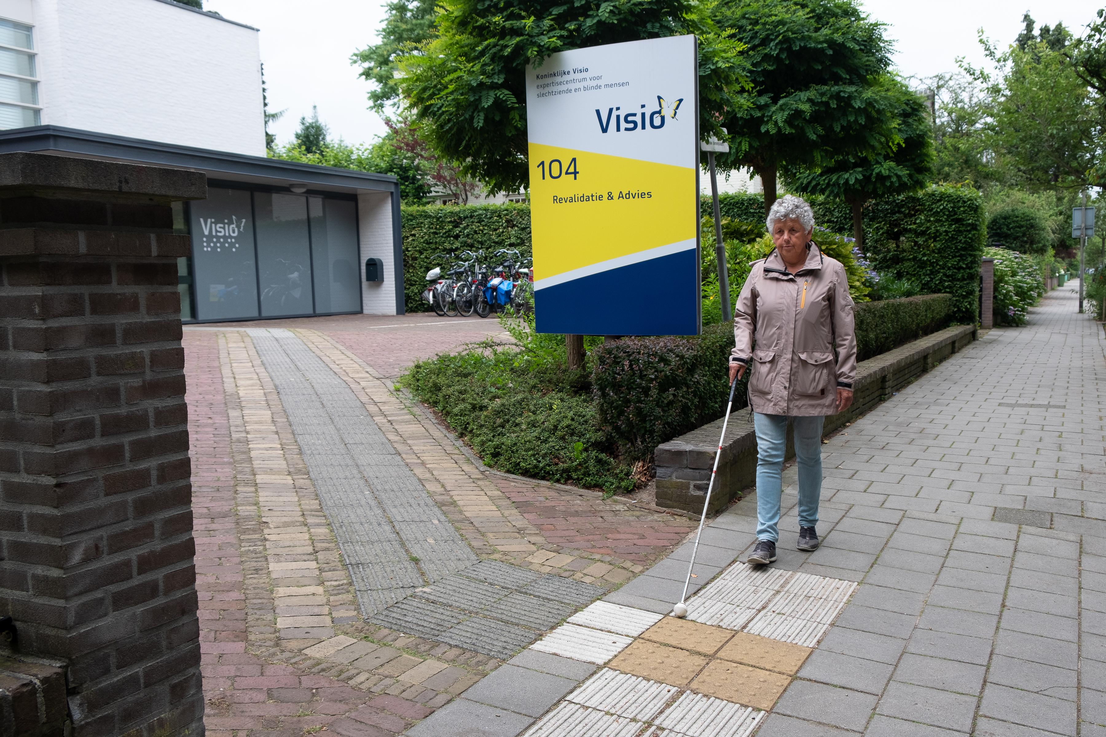 Blinde vrouw loopt met taststok over geleidelijn bij Visio Nijmegen Revalidatie en Advies